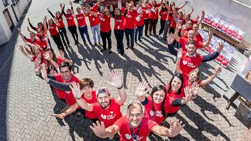 Group of people wearing stop hunger t-shirts standing in the shape of a heart and waving